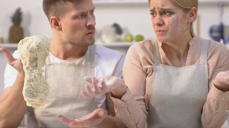 kézzel készített : Man angrily looking at soiled in flour wife, holding bad dough in hands, failure Stock mozgókép