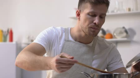 суп : Handsome man in apron cooking, stirring ingredients in pan and trying meal
