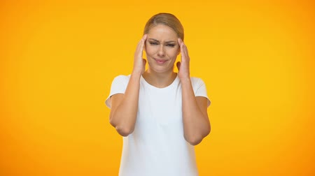 мигрень : Young lady suffering headache on bright background, temple spasm, health care Стоковые видеозаписи