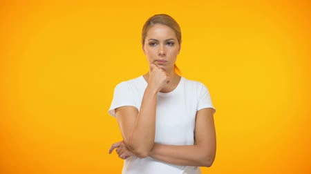 hloupý : Thoughtful female with hand on chin standing on orange background, hesitation