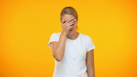 facepalm : Stressed woman showing face palm gesture, covering eyes by hands, disappointment Stock Footage