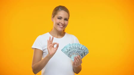 ücretli : Positive female showing ok gesture holding dollars in hand, financial investment
