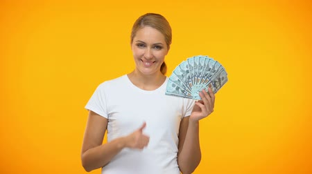 piyango : Cheerful woman showing thumbs up holding dollars in hand, well paid job, profit