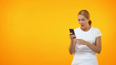 igen : Happy young woman pointing at smartphone hand, easy credit, online application
