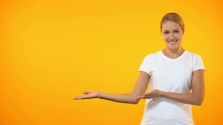 female hands : Young smiling woman presenting template on orange background, announcement