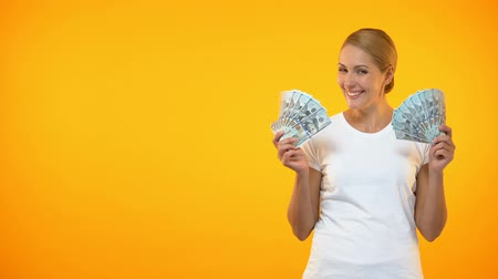 ganhos : Excited woman showing dollar bills on orange background, lottery win, income.
