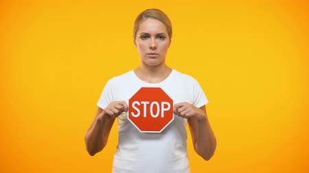 proibir : Caucasian female holding stop sign in hands, restriction symbol, warning danger