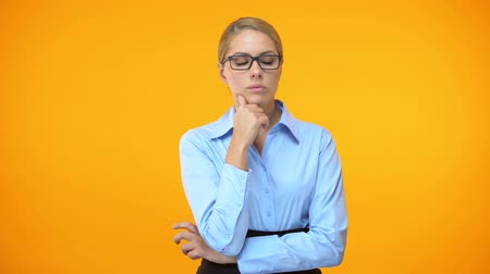 thought : Thoughtful woman looking right and left on orange background, difficult choice