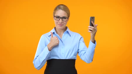 tariff : Caucasian business lady showing thumbs up holding smartphone hand, application Stock Footage
