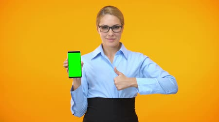 prohlížeč : Female company employee showing thumbs up holding smartphone with green screen Dostupné videozáznamy