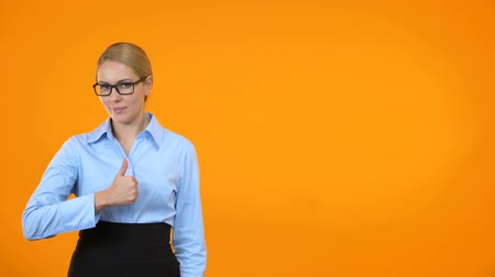ajánlás : Beautiful young woman in eyeglasses showing thumbs up on orange background