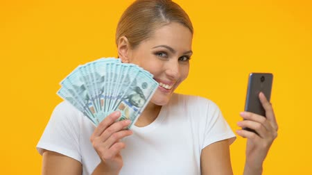 piyango : Cheerful woman holding smartphone and bunch of dollars, online banking service