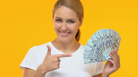 arbeidsomstandigheden : Cheerful woman pointing finger at bunch of dollars, profitable credit terms Stockvideo