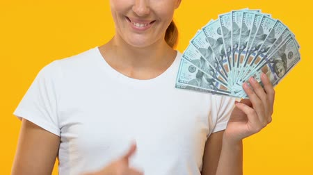 rentável : Happy lady holding bunch of dollars and showing thumbs up, salary and benefits Vídeos