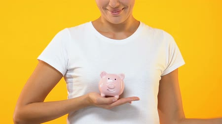 mevduat : Smiling female holding piggy bank, family budget, savings for future investment