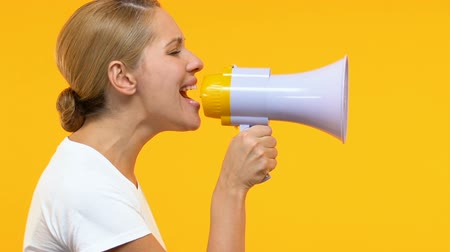 megafono : Serious woman shouting in megaphone, announcing information, social protest Filmati Stock