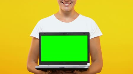 monitor počítače : Cheerful woman showing laptop with green screen into camera, online shopping Dostupné videozáznamy