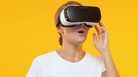 приложение : Wondered woman in virtual reality headset enjoying modern technology, future
