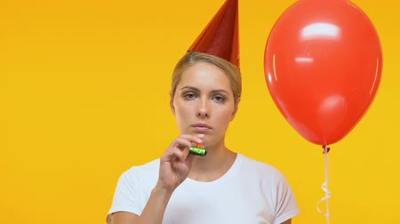 bóia : Upset lady in birthday hat holding balloon and blowing in party horn, loneliness