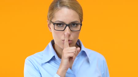 evasion : Beautiful business lady showing silence sign and winking, corporative secret Stock Footage