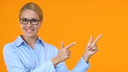 szigetelés : Smiling female manager pointing fingers into orange background template for text Stock mozgókép