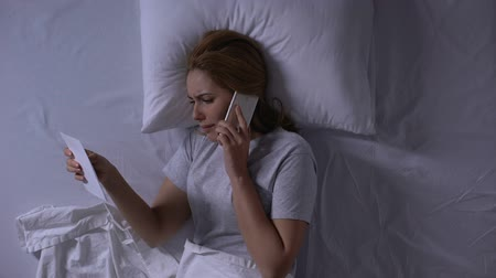 запомнить : Woman trying to call to her man lying in bed and looking at photo, betrayal