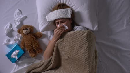 dokular : Lonely sick woman hugging toy bear lying in bed with compress and tissues