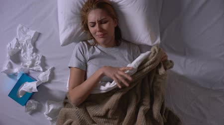 dokular : Depressed woman loudly crying lying in bed and stroking sheet, pain of loss