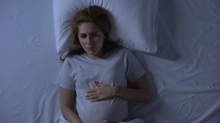 to be alone : Lonely expecting woman crying in bed stroking belly, hopelessness, depression Stock Footage