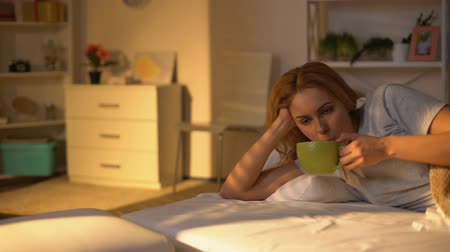 probudit se : Relaxed happy woman drinking coffee lying in bed, rest on weekend morning, peace Dostupné videozáznamy
