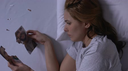 separado : Lonely woman in bed holding pieces of torn photo and crying, husband betrayal