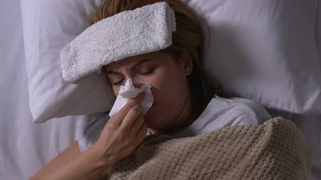 doku : Sick woman with towel on forehead lying in bed, coughing and blowing nose, flu Stok Video