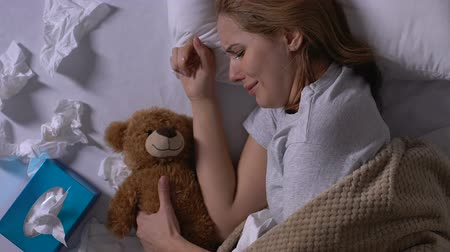 bídný : Crying woman hugging teddy bear, used napkins on bed, loneliness after break up