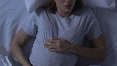 szülői : Pregnant woman holding tummy and turning in bed, uncomfortable sleeping