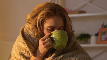 cold : Sick woman covered in blanket drinking hot tea, non-traditional treatment