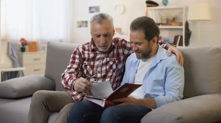 photo album : Adult father and son viewing old photos sharing good memories family traditions Stock Footage