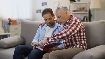 remember : Pensive adult males holding album and viewing photos, recalling relatives