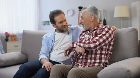 запомнить : Cheerful adult males sharing memories father and son joking and having good time