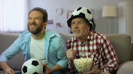 parentes : Anxious adult males watching football match on tv, unhappy about team losing
