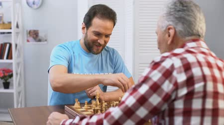 dobrovolník : Middle aged male volunteer playing chess with elderly man in nursing home, hobby