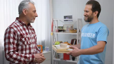 пожертвование : Volunteer bringing aged senior male tray with breakfast, helping in nursing home