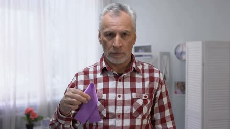 refah : Senior male showing purple ribbon to camera, Alzheimer disease awareness, care