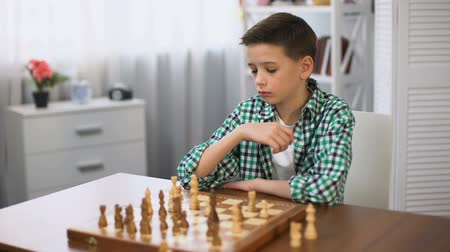 tattica : Bored schoolboy playing chess and looking at watch, unwilling to continue