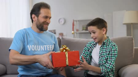 voluntary : Young volunteer giving boy birthday present, social adaptation for orphans, care