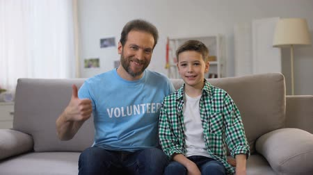 voluntary : Smiling middle-aged volunteer and schoolboy shoving thumbs-up to camera, ad Stock Footage