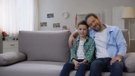 poll : Happy smiling dad and schoolboy son sitting on sofa, looking to camera, family Stock Footage