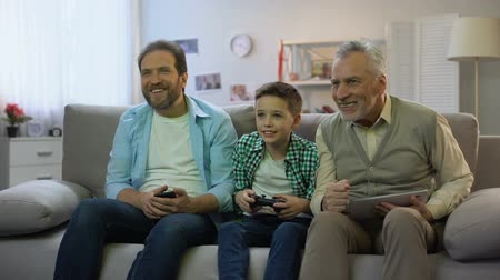 konsola : Granddad and dad cheering for boy playing video game, hobby and leisure activity