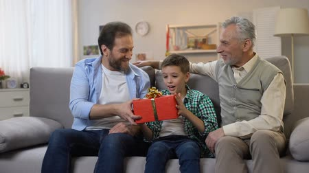 bóia : Granddad and dad congratulating preteen boy, giving birthday present in box Stock Footage
