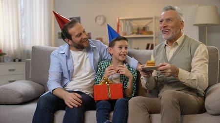 bóia : Middle-aged male and preteen boy congratulating grandpa with anniversary, family Stock Footage