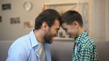 together trust : Smiling father and little son touching foreheads, trustful relations. Stock Footage